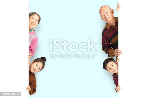 istock happy Family posing  behind blank white board 1094850726