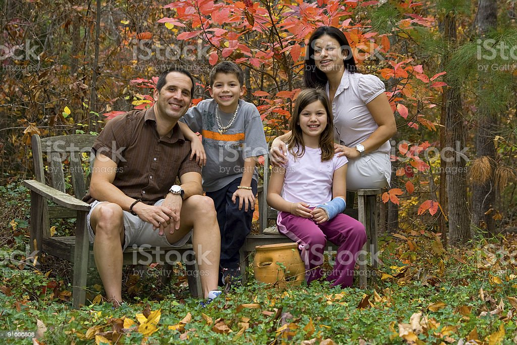Happy family posing in a fall garden landscape royalty-free stock photo