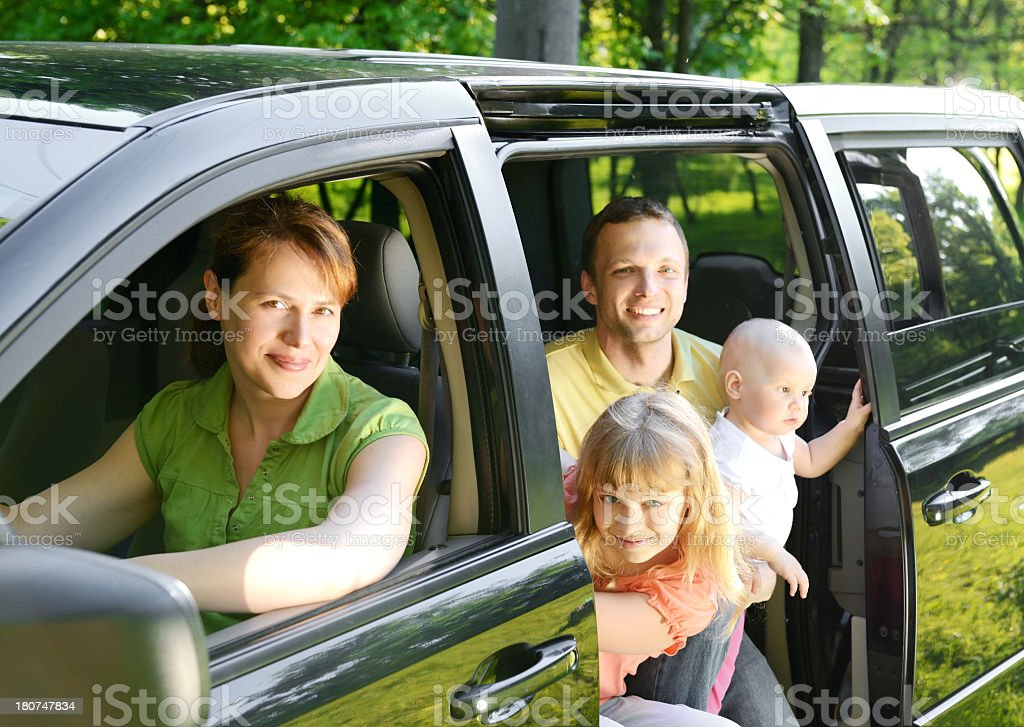 A happy family posing inside a van royalty-free stock photo