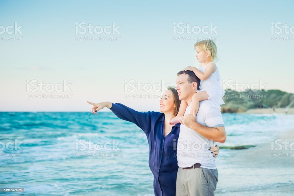 Happy family- pregnant mother, father and daughter embracing each other and watching ahead to the sea during walk on the beach. Relax by the calm sea in sunshine. Family vacation. Selective focus. - Royalty-free Adult Stock Photo