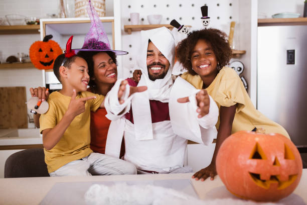 Happy family preparing for Halloween, having fun. stock photo