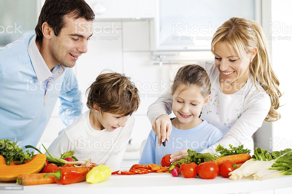 Happy family preparing meal together in the kitchen. royalty-free stock photo