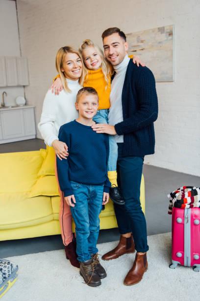 glückliche familie bereit für winterferien und blick in die kamera mit gepackten koffer reisen konzept - kleinkind busy bags stock-fotos und bilder