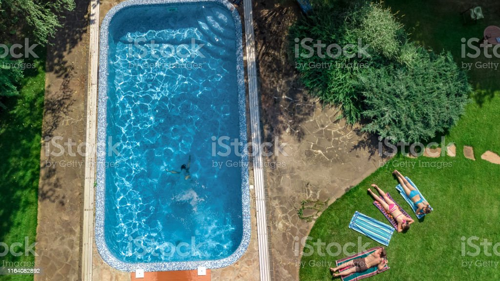 Happy family relaxing by swimming pool, aerial drone view from above...