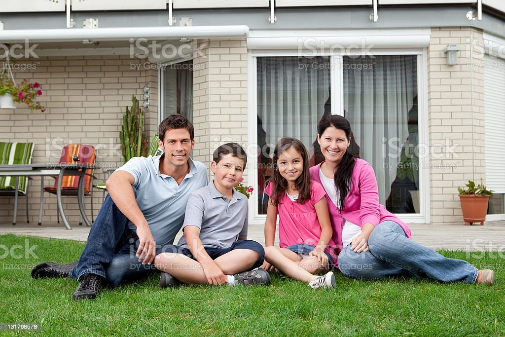 Happy family relaxing in backyard of new home royalty-free stock photo