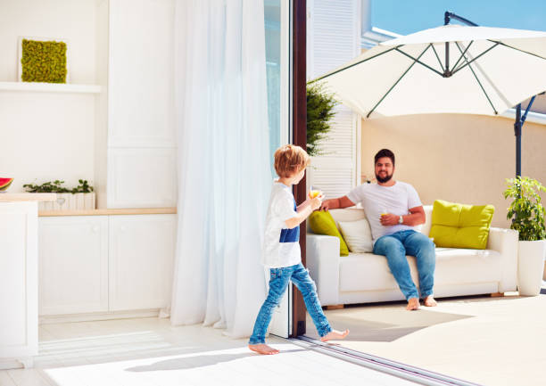 happy family relaxing on rooftop patio with open space kitchen at warm summer day stock photo