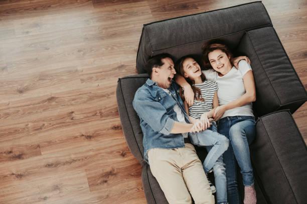 Fröhliche Familie entspannt gemeinsam auf der Couch zu Hause – Foto