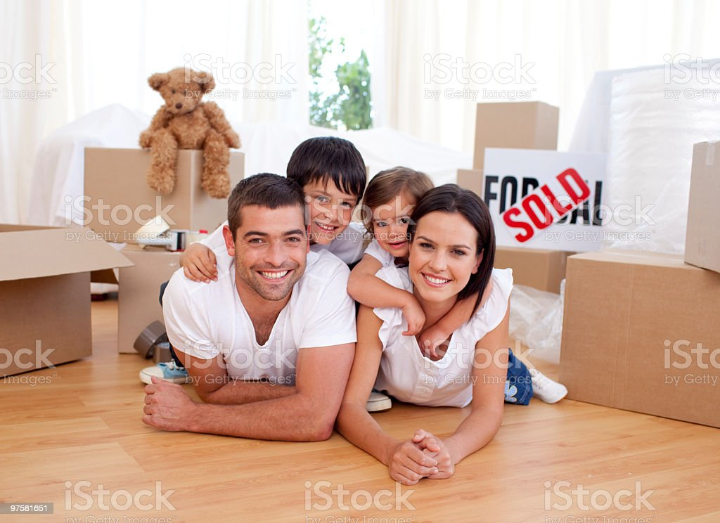 Happy family relaxing while moving house royalty-free stock photo