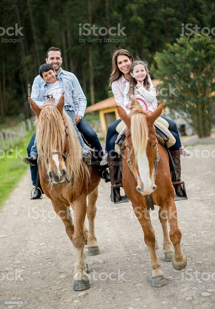 Happy family riding horses stock photo