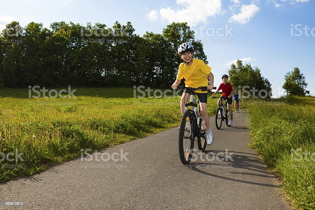 A happy family riding their bikes on a country road stock photo