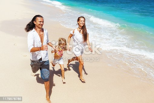 849648098 istock photo Happy family run together along sea surf on tropical beach 1179578785