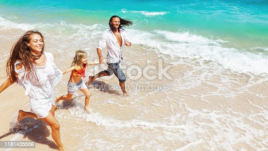849648098 istock photo Happy family run together along sea surf on tropical beach 1181435556