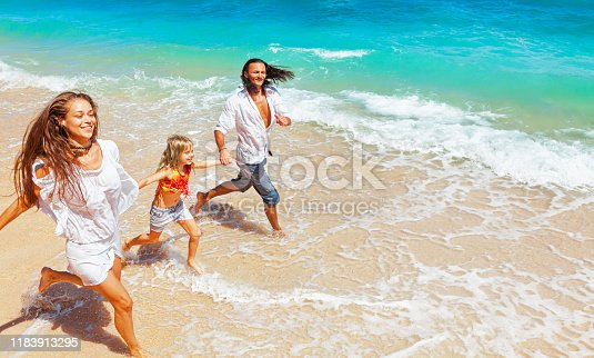 849648098 istock photo Happy family run together along sea surf on tropical beach 1183913295