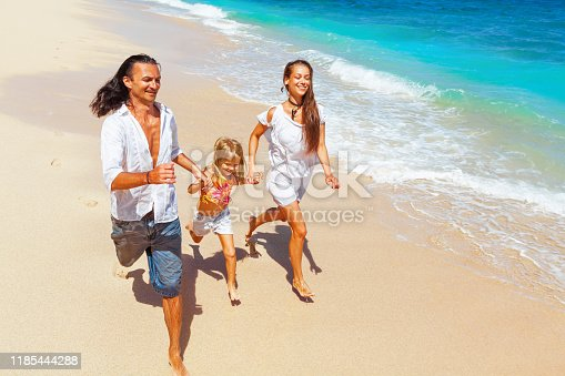 849648098 istock photo Happy family run together along sea surf on tropical beach 1185444288