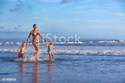 849648098 istock photo Happy family run with fun along sunset beach surf 531699976