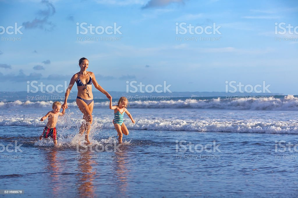 Happy family run with fun along sunset beach surf stock photo
