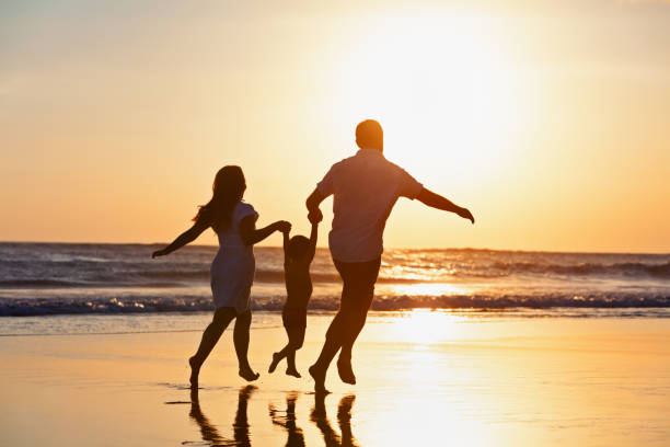 Happy family running by sunset beach Happy family black silhouette on sun background. Father, mother, baby son run. Child jump with fun by water pool along sea surf on beach. Travel lifestyle, parents walking with kid on summer vacation. lesser sunda islands stock pictures, royalty-free photos & images