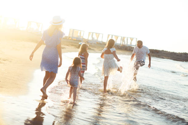 Happy family running in sea water stock photo