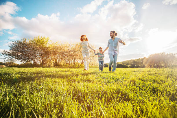 Happy family running in the park stock photo