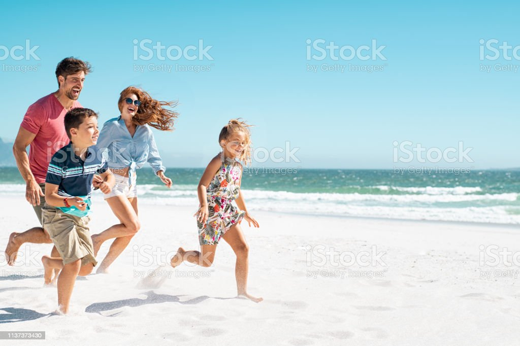 Happy family running on beach Cheerful young family running on the beach with copy space. Happy mother and smiling father with two children, son and daughter, having fun during summer holiday. Playful casual family enjoying playing at beach during vacaton. 8-9 Years Stock Photo