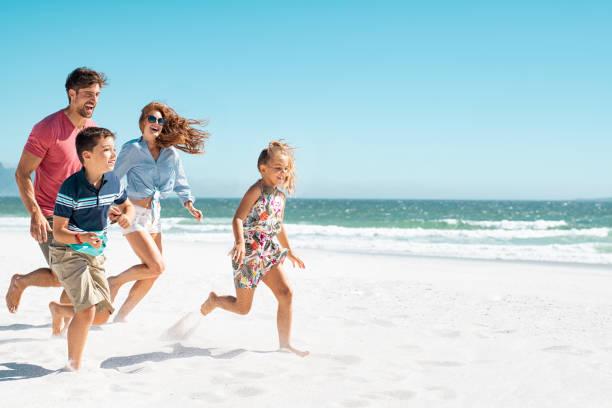 familia feliz corriendo en la playa - playa fotografías e imágenes de stock