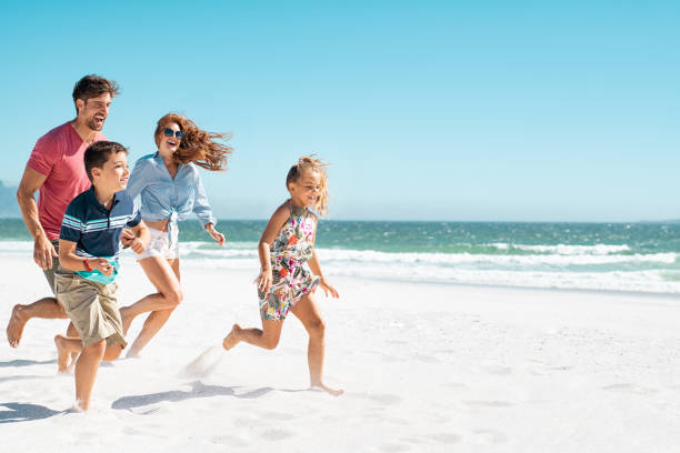 Happy family running on beach Cheerful young family running on the beach with copy space. Happy mother and smiling father with two children, son and daughter, having fun during summer holiday. Playful casual family enjoying playing at beach during vacaton. holidays stock pictures, royalty-free photos & images