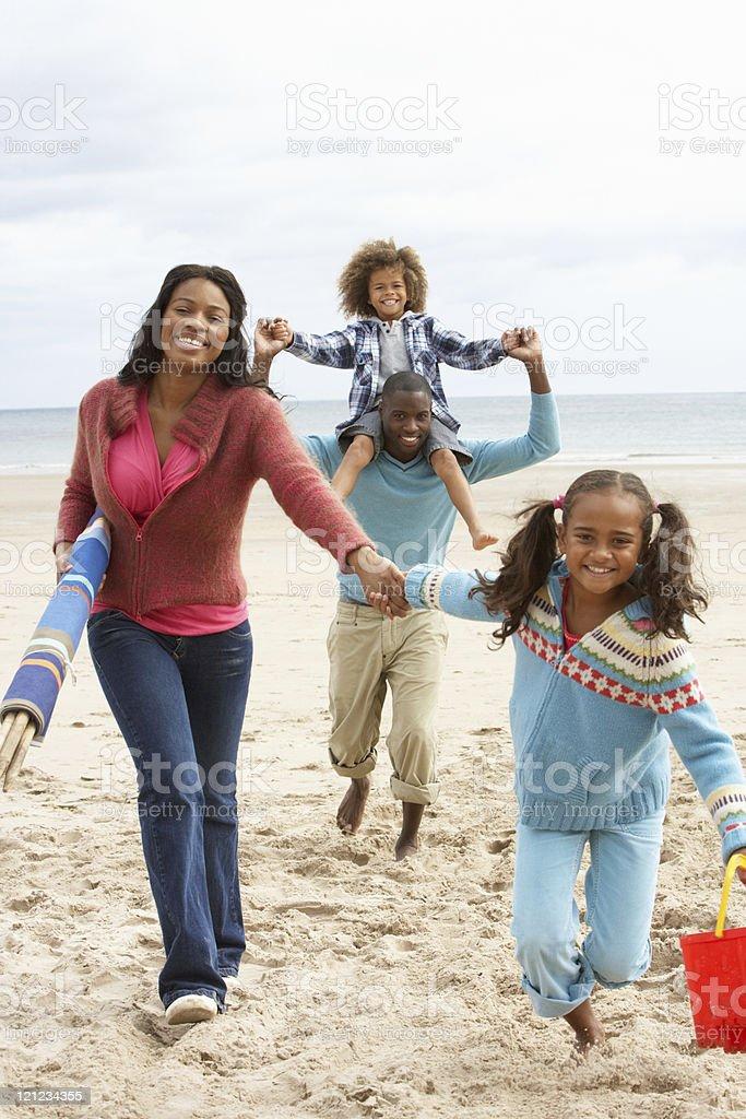 Happy family running on beach stock photo