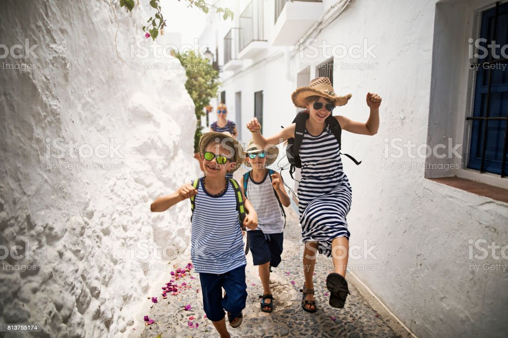 Happy family running on street in andalusian white village stock photo
