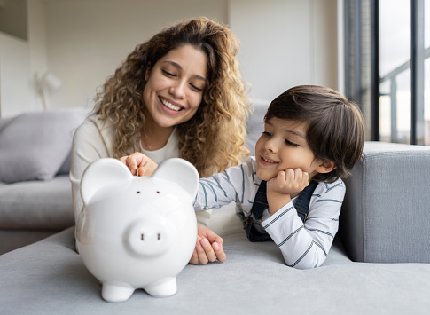 Portrait of a happy Latin American single-parent-family saving money in a piggybank - home finances concepts