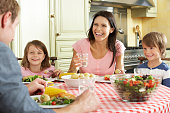 Family Eating Meal Together In Kitchen Smiling And Laughing.