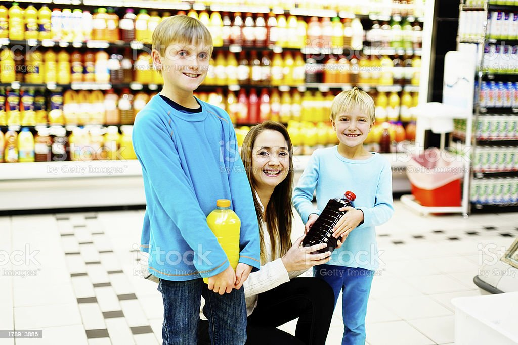 Happy family shop for healthy fresh fruit juice in supermarket royalty-free stock photo