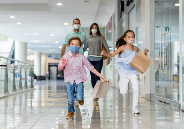Happy family shopping at the mall during the pandemic wearing facemasks stock photo