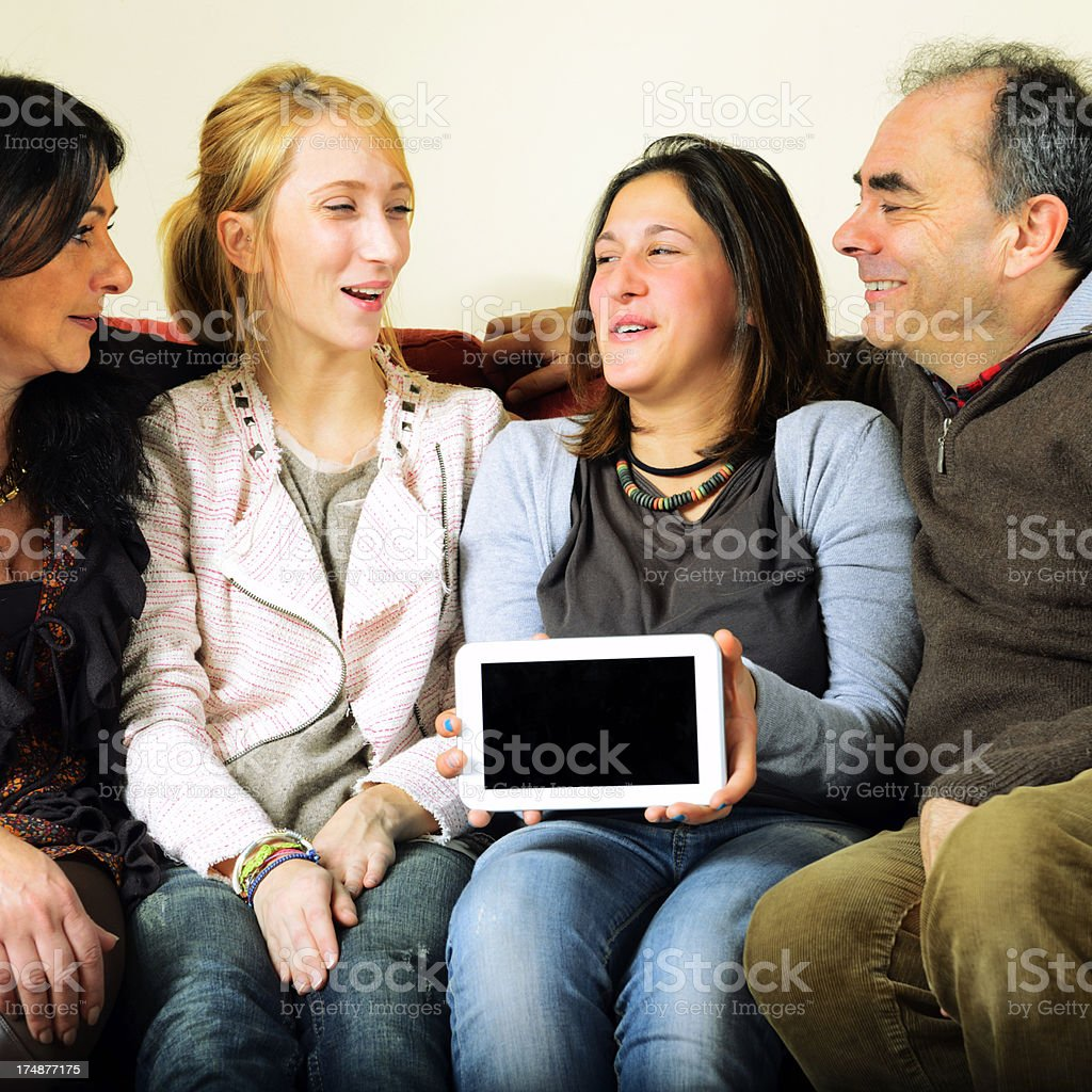 Happy Family Showing Digital Tablet on Sofà royalty-free stock photo