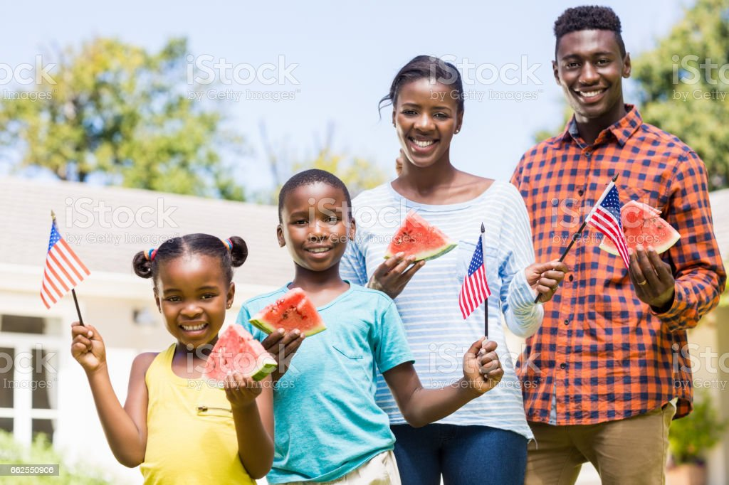 Happy family showing usa flag and eating watermelon stock photo