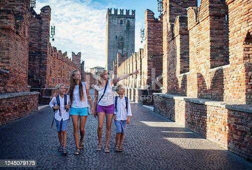 Family sightseeing beautiful Italian town of Verona. Mother and three kids are walking on Ponte Scaligero bridge towards the old town centre. Sunny summer day in Verona, Veneto, Italy. Nikon D850