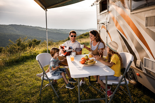 Happy family having fun while singing at picnic table by the camper trailer in nature. Man is playing a guitar.