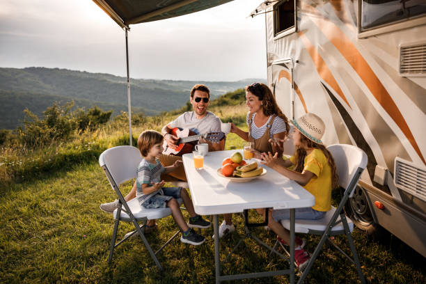 Happy family signing during their camping day by the trailer. stock photo