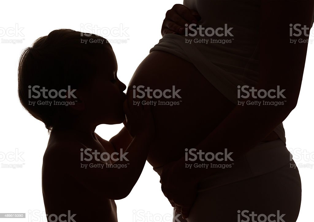 Happy family. Silhouette  of child kissing  belly of pregnant mo stock photo