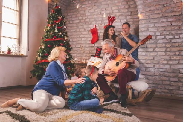 Happy family singing Christmas songs stock photo