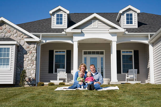 Happy family sit outside new houses on lawn posing for photo stock photo