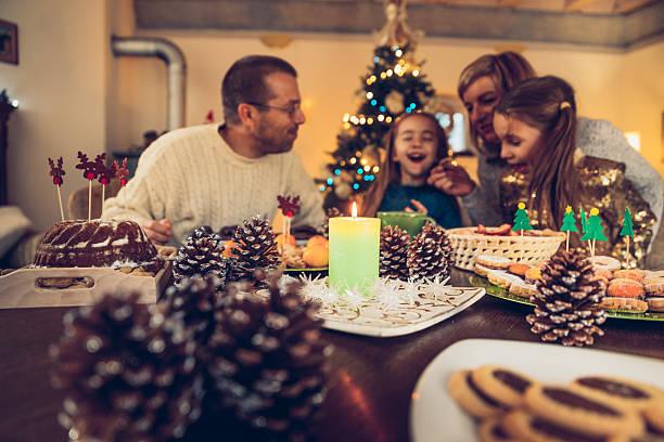 happy family sitting at the table after the christmas dinner - kinderzimmer tischleuchten stock-fotos und bilder