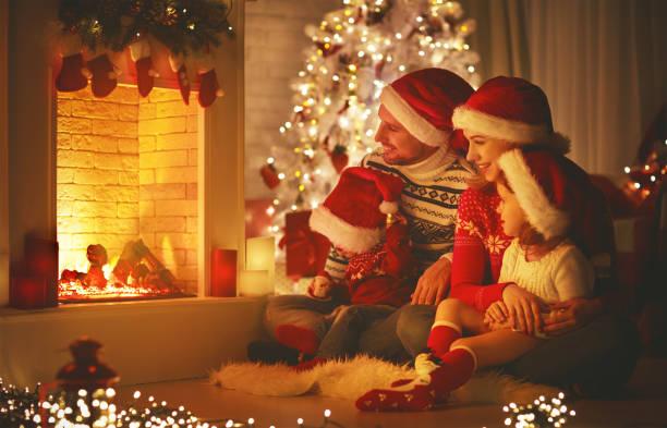 glückliche familie am heiligabend kamin sitzen - kinder weihnachtsfilme stock-fotos und bilder