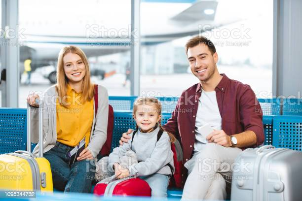 Happy family sitting in departure lounge and smiling near luggage in picture id1095344732?b=1&k=6&m=1095344732&s=612x612&h=vmcjheiljthfry1hjkbyschzvhwzrphieaox0vmowha=