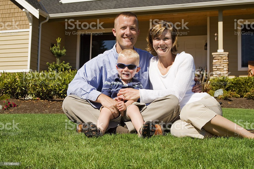 Happy Family sitting in front of their home royalty-free stock photo