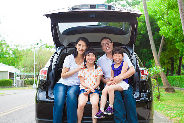 happy family sitting in the car and their house behind stock photo