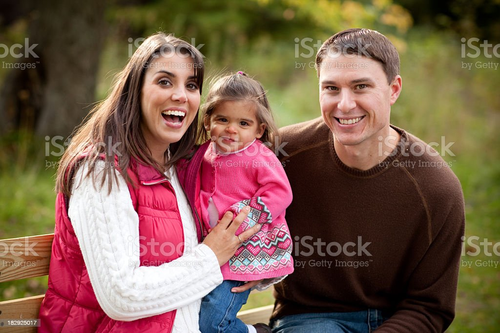 Happy Family Sitting on Bench in Woods During Autumn royalty-free stock photo