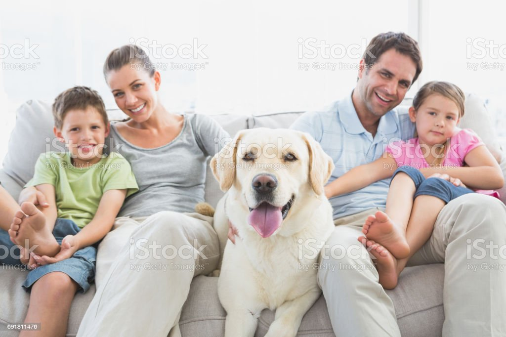 Happy family sitting on couch with their pet labrador stock photo