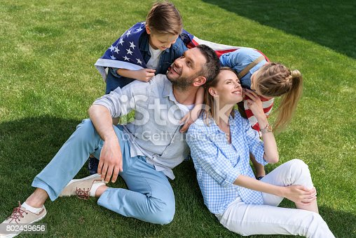 istock Happy family sitting on grass with american flag, celebrating 4th july - Independence Day 802439656