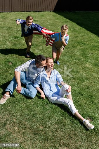 istock Happy family sitting on grass with american flag, celebrating 4th july - Independence Day 802443292