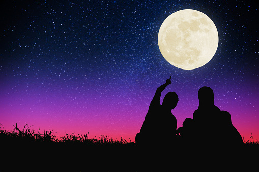 happy family sitting on hill and watching the moon and star .Celebrate Mid-autumn festival
